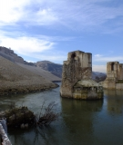 (on the right) The Old Hasankeyf Bridge (on the left) the stone wall that seals the historical caves, which are now filled with debris.
