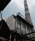 The chimney of Line 1 of the Phả Lại Power Station looms in the background. Line 1 doesn't have flue-gas desulfurization installed to capture sulfur emissions, causing major health issues for workers.